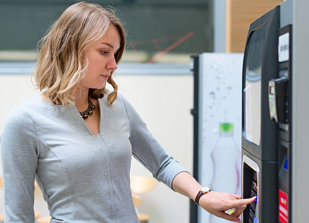 Woman using touch screen vending machine