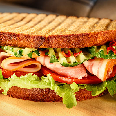 Granilled panini sandwich with tomatoes, lettuce and fresh cucumbers